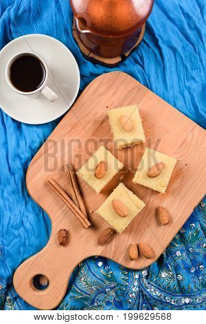 Flour halava with almonds served on indigo cloth with black coffee. Indian cuisine vertical