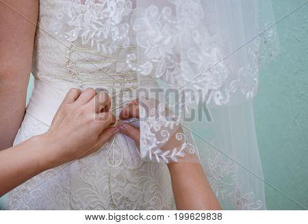 Bridesmaid helps to bride dress in wedding day.