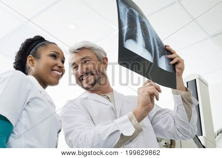 Smiling Radiologists Analyzing Chest X-ray In Examination Room