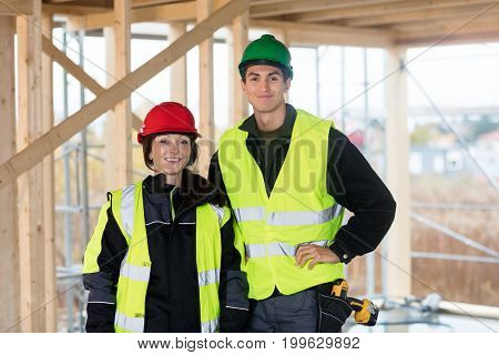 Confident Carpenters Wearing Reflective Jackets At Site
