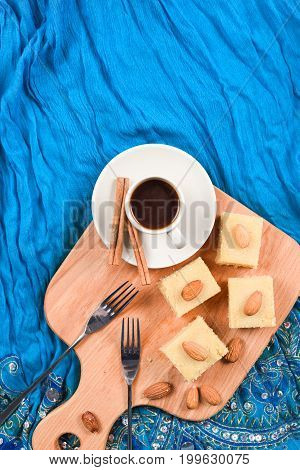 Indian dessert halava with almonds served with coffee on indigo cloth copyspace vertical