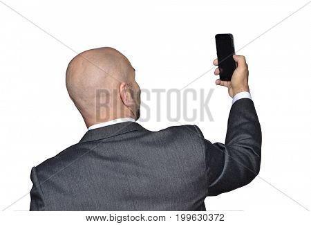 Back view from a bald head businessman taking selfie picture with smart phone.