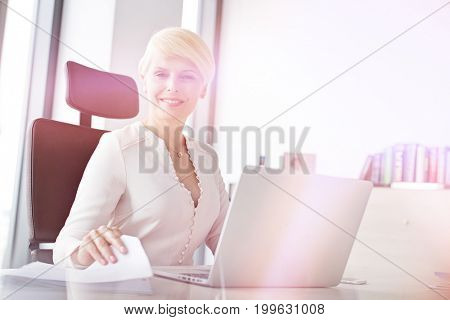 Portrait of smiling mature businesswoman with laptop and document at office desk