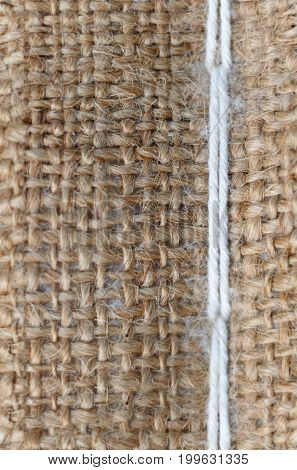 vertical seamless texture of burlap with white thread