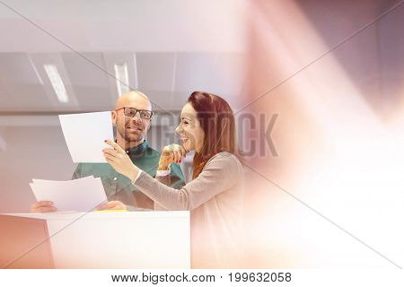 Businessman and businesswoman discussing over documents in office
