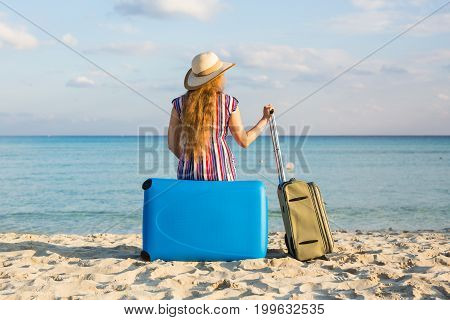 Freedom, travel, vacation and summer concept - Traveler woman with suitcases back view.
