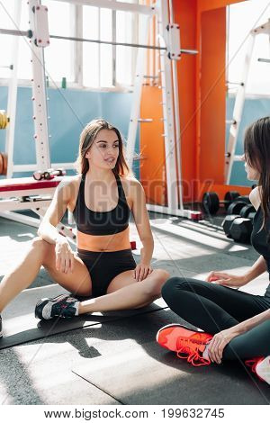 fitness sport training gym and lifestyle concept - two smiling women sitting on the half ball and relaxing after class in the gym