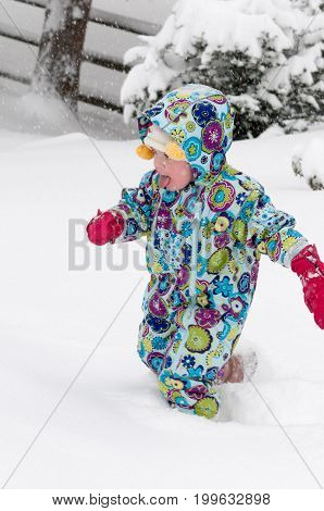 View of happy toddler girl in warm coat and knitted hat tossing up snow and having a fun in the winter outside, outdoor portrait
