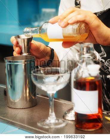 Bartender is pouring homemade infusion into a mixing glass, making cocktail, toned image