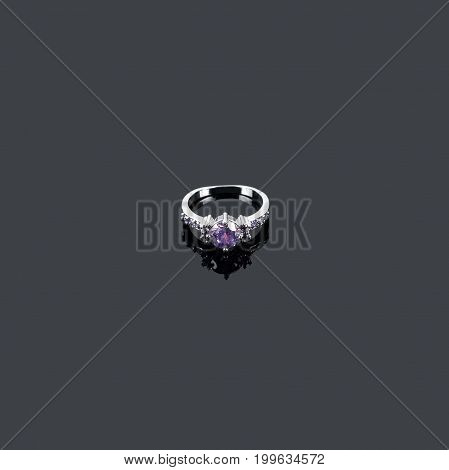 Amethyst ring, jewelery with precious gems, diamond and gemstone isolated on black reflective background