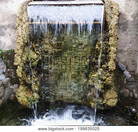 Small waterfall in the Park. Transparent falling water. clear water.