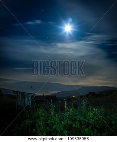 A farmyard at spooky night illuminated with full moon and stars glowing through overcast skies in background
