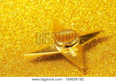 Gold spinner in the form of a star on a sparkling gold background. Spinner moves. The concept of the spinner's trend wealth success luxury