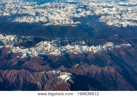 Aerial view of european mountains (Alps) with with summits covered with snow as seen from airplane.