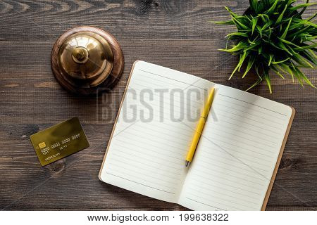 Book hotel. Service bell and notebook at the reception on dark wooden table top view.