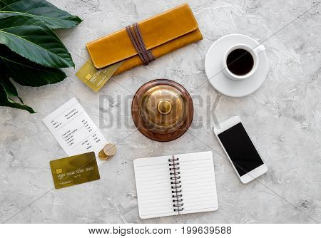 Pay bill at cafe by card. Purse, bill and bank card near coffee cup on grey stone table top view.