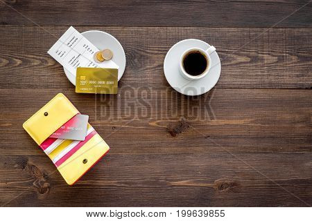 Restaurant bill, purse and bank card near cup of coffee on dark wooden table top view.