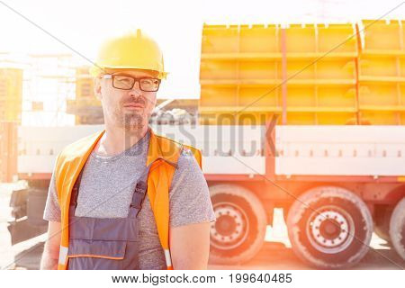 Thoughtful architect standing against truck at construction site