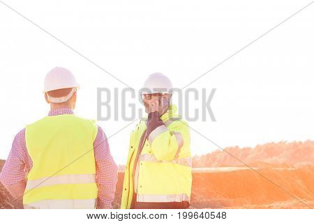 Male engineer using mobile phone while standing with colleague at construction site against clear sky