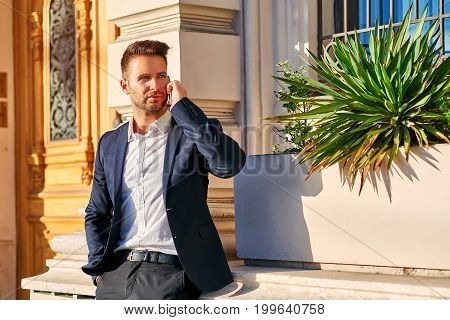 A handsome young businessman leaning against the wall at the entrance of a building while talking on his phone in the sunshine