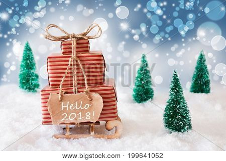 Sleigh Or Sled With Christmas Gifts Or Presents. Snowy Scenery With Snow And Trees. Blue Sparkling Background With Bokeh Effect. Label With English Text Hello 2018 For Happy New Year