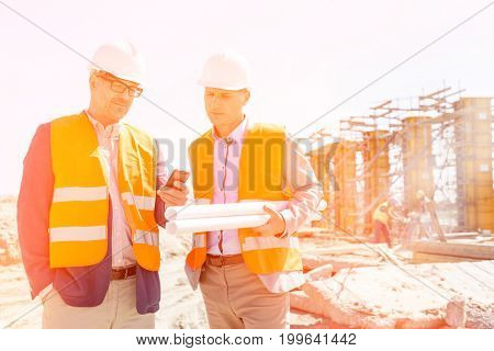 Male engineers using mobile phone at construction site against clear sky