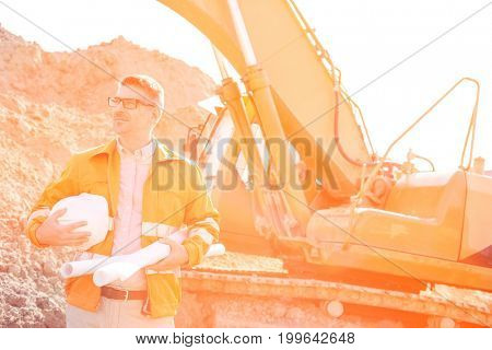 Confident architect holding hardhat and blueprints at construction site