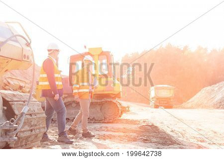 Supervisors walking at construction site against clear sky