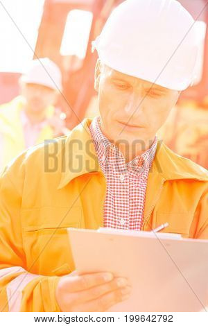 Supervisor writing on clipboard at construction site with colleague in background