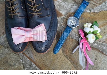Top View Of Pink Bowtie On Blue Leather Groom Shoes Near Watches And Boutonniere On Brown Natural St