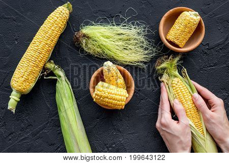 Woman's hands clean corn cob. Black stone background top view.