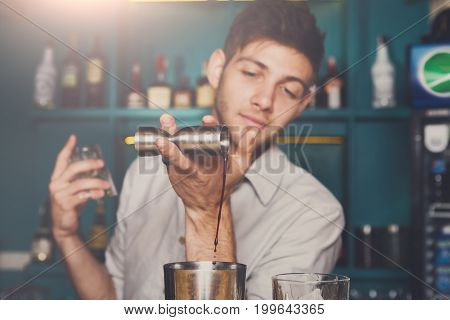 Unrecognizable bartender in bar interior pouring syrup into shaker for making cocktail. Service industry occupation.