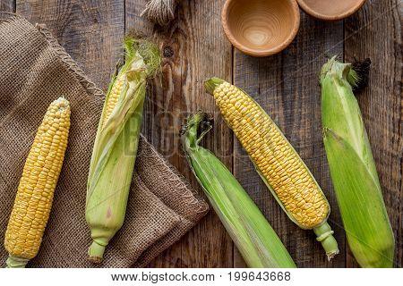Vegetarian food. Corn cobs on rustic wooden background top view.