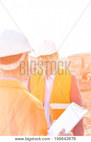 Happy engineers discussing at construction site against clear sky