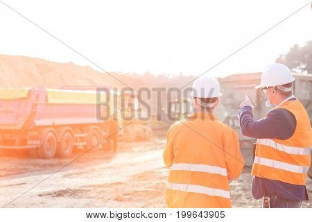 Supervisor explaining plan to colleague at construction site