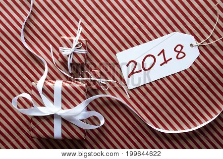 Two Gifts Or Presents With White Ribbon. Red And Brown Striped Wrapping Paper. Christmas Or Greeting Card. Label With English Text 2018 For Happy New Year