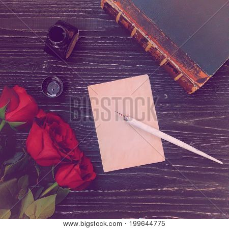 Blank sheet of paper with a dip pen ink-pot ancient book and three red roses on a worn black wooden background view from the top or flat lay (specially toned in a retro style)