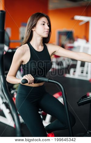 Woman 20S Wearing Smart Watch Working Out On Exercise Bike