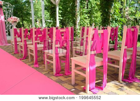 Wedding Chairs On Each Side Of Archway. Place For Wedding Ceremony Decorated In Pink Color,  Wooden