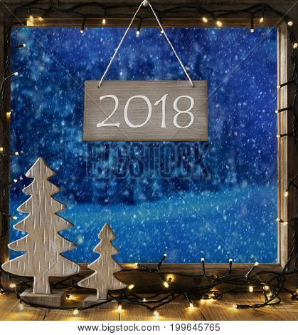 Sign With Text 2018. Window Frame With Winter Landscape With Snow. View To Snowy Trees Outside With Snowflakes. Christmas Tree And Fairy Lights.