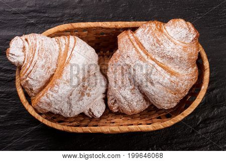 two croissant sprinkled with powdered sugar in a wicker basketon black stone background closeup. Top view.