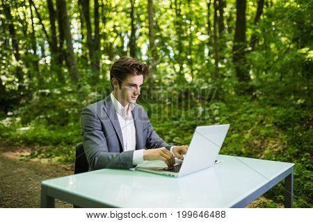 Businessman Sitting At The Office Desk Work At Laptop Computer In Green Forest Park. Freelancer Work