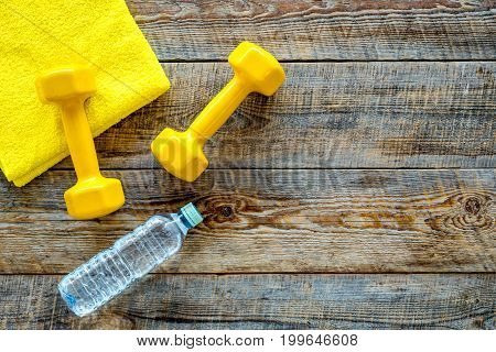 Fitness background. Dumbbells, towel and water on wooden background top view.