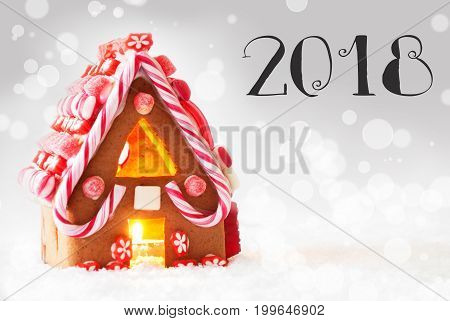 Gingerbread House In Snowy Scenery As Christmas Decoration. Candlelight For Romantic Atmosphere. Silver Background With Bokeh Effect. English Text 2018 For Happy New Year