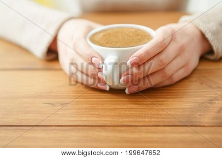 Female holding a cup of coffee while sitting at wooden table, shallow depth of field.