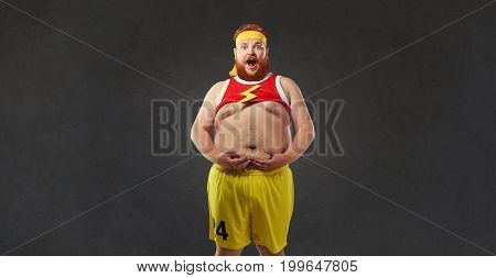 Fat man in sports clothes is holding his stomach. Humor sport concept.
