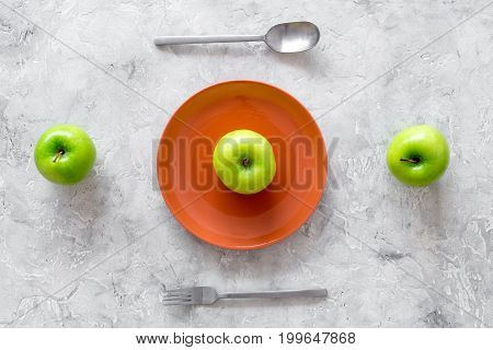 Slimming diet. Apple at plate on grey stone background top view.
