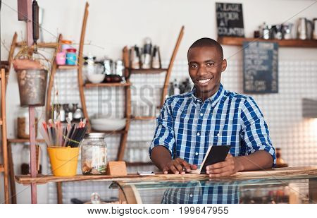 Portrait of a smiling young African entrepreneur standing at the counter of his trendy cafe writing down notes in a book