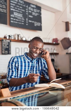 Smiling young African entrepreneur standing at the counter of his cafe talking on a cellphone and writing in a notebook