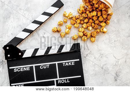 Popcorn for watching fim near clapperboard on grey background top view.